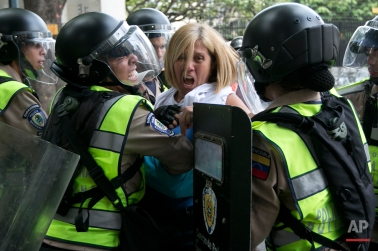 An anti-government demonstrator is pushed away by Bolivarian National Police who block protesters from reaching the headquarters of the national electoral body, CNE, in Caracas, Venezuela, Wednesday, May 18, 2016. The opposition was blocked from marching to the CNE as they demand the government allow it to pursue a recall referendum against Venezuela's President Nicolas Maduro. (AP Photo/Ariana Cubillos)