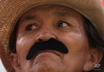 A supporter of Venezuela's President Nicolas Maduro, wears a fake moustache depicting him, during a women's march for peace at Miraflores Presidential Palace in Caracas, Venezuela, Tuesday, May 24, 2016. Maduro is facing a movement by the opposition to force a referendum to recall him from office. (AP Photo/Ariana Cubillos)