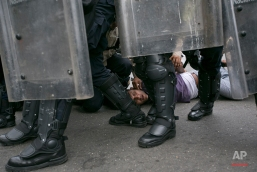 An anti-government protester is detained by Bolivarian National Police who blocked protesters from reaching the headquarters of the national electoral body, CNE, in Caracas, Venezuela, Wednesday, May 18, 2016. The opposition is demanding the government allow it to pursue a recall referendum against Venezuela's President Nicolas Maduro. (AP Photo/Ariana Cubillos)
