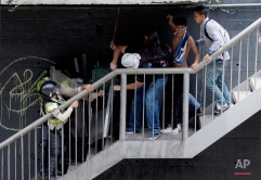 Anti-government demonstrators fight with Bolivarian National police on a pedestrian bridge during an anti-government march toward the headquarters of the national electoral body, CNE, in Caracas, Venezuela, Wednesday, May 18, 2016. The opposition was blocked from marching to the CNE as they demand the government allow it to pursue a recall referendum against Venezuela's President Nicolas Maduro. (AP Photo/Fernando Llano)