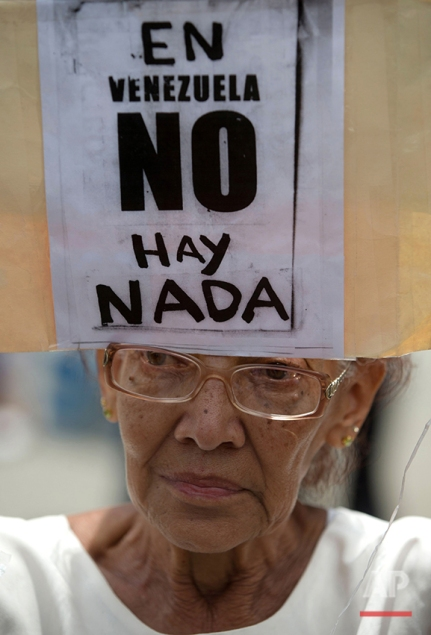 """An anti-government demonstrator holds a sign that reads in Spanish: """"In Venezuela there's nothing,"""" in reference to food shortages, during a march to the headquarters of the national electoral body, CNE, in Caracas, Venezuela, Wednesday, May 18, 2016. Opposition marchers were blocked from reaching the CNE to demand the government allow it to pursue a recall referendum against Venezuela's President Nicolas Maduro. (AP Photo/Fernando Llano)"""