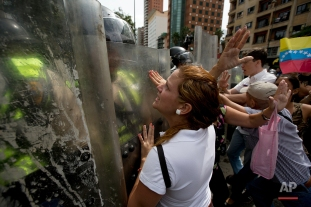 Anti-government demonstrators argue with Bolivarian National Police blocking them from reaching the headquarters of the national electoral body, CNE, in Caracas, Venezuela, Wednesday, May 18, 2016. The opposition was blocked from marching to the CNE to demand the government allow it to pursue a recall referendum against Venezuela's President Nicolas Maduro. (AP Photo/Fernando Llano)