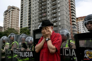 An anti-government demonstrator wipes his face after Bolivarian National Police fired tear gas to block protesters from reaching the headquarters of the national electoral body, CNE, in Caracas, Venezuela, Wednesday, May 18, 2016. The opposition is demanding the government allow it to pursue a recall referendum against Venezuela's President Nicolas Maduro. (AP Photo/Ariana Cubillos)