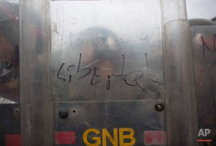 """A National Guard soldier's shield is covered by the Spanish message: """"I love you, freedom,"""" written by a protester during an anti-government march in Caracas, Venezuela, Wednesday, May 11, 2016. The opposition is marching to demand election officials start counting signatures that could lead to a presidential recall vote. (AP Photo/Ariana Cubillos)"""