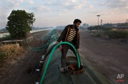 """In this Monday, May 9, 2016, photo, a worker fills water in one of the many tanks of the Jaldoot water train at the Miraj railway station, Miraj, 340 kilometers (212 miles) from Latur, in the Indian state of Maharashtra. Many trains pull into Latur's railroad station but none is as eagerly awaited as this train that pulls into the parched town in the dead of the night. That train called """"Jaldoot"""" or the Messenger of Water brings millions of liters of the precious liquid that the drought-plagued central Indian district so desperately needs. (AP Photo/Manish Swarup)"""