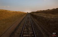 """In this Monday, May 9, 2016, photo, parched land is seen on the both sides of railway track as Jaldoot water train makes it way to Latur from Miraj railway station, Miraj 340 kilometer (212 miles) from Latur, in the Indian state of Maharastra. Many trains pull into Latur's railroad station but none is as eagerly awaited as the train that pulls into the parched town in the dead of the night. That train called """"Jaldoot"""" or the Messenger of Water brings millions of liters of the precious liquid that the drought-plagued central Indian district so desperately needs. (AP Photo/Manish Swarup)"""