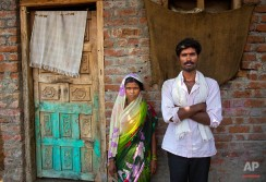 In this May 11, 2016, photo, sugarcane workers Vijay Abhiman Kasbe and his wife Meera Vijay Kasbe who have found themselves trapped between middlemen who hired them and farm owners who paid for the labor, stand outside their house after their return in Telgaon village, in Marathwada region, in the Indian state of Maharashtra. Failed monsoons play havoc with millions of farmers in central India leading to crippling poverty and soaring suicides. (AP Photo/Manish Swarup)