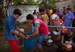 """In this Tuesday, May 10, 2016, photo, residents of a shanty town fill water from municipal taps, whose supply is provided by the Jaldoot water train in Latur, in the Indian state of Maharastra. Many trains pull into Latur's railroad station but none is as eagerly awaited as the train that pulls into the parched town in the dead of the night. That train called """"Jaldoot"""" or the Messenger of Water brings millions of liters of the precious liquid that the drought-plagued central Indian district so desperately needs. (AP Photo/Manish Swarup)"""