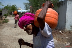 In this May 10, 2016, photo, a villager carries a water pot on his shoulder in Marathwada region, in the Indian state of Maharashtra. Failed monsoons play havoc with millions of farmers in central India leading to crippling poverty and soaring suicides. Some 400 farmers have killed themselves so far this year in the parched Marathwada region, which is home to about 19 million people. (AP Photo/Manish Swarup)