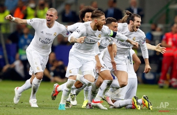 Real Madrid players celebrate after Cristiano Ronaldo scored the winning penalty in a shootout during the Champions League final soccer match between Real Madrid and Atletico Madrid at the San Siro stadium in Milan, Italy, Saturday, May 28, 2016. Real Madrid won 5-4 on penalties after the match ended 1-1 after extra time. (AP Photo/Antonio Calanni)