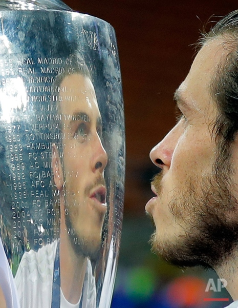 Real Madrid's Gareth Bale holds the trophy after the Champions League final soccer match between Real Madrid and Atletico Madrid at the San Siro stadium in Milan, Italy, Saturday, May 28, 2016. Real Madrid won 5-4 on penalties after the match ended 1-1 after extra time. (AP Photo/Manu Fernandez)