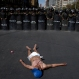 A protester demanding an increase in state benefits for people with disabilities, lies on a paved street before a cordon of police who are serving as a barricade to keep protesters from blocking anymore streets, in La Paz, Bolivia, Thursday, June 2, 2016. Some protesters donned diapers hoping to call attention to disabled people who are demanding that their annual state benefits of 1,000 Bolivianos be increased to a monthly stipend of 500 Bolivianos, or about $73 dollars. (AP Photo/Juan Karita)