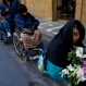A woman in a wheelchair carries flowers behind two mock coffins, symbolizing protesters who died yesterday in La Paz, Bolivia, Friday, June 10, 2016. The two protesters were run over by a drunk driver as they slept in their encampment in Cochabamba, one of many cities where disabled people are carrying out an ongoing protest to demand an increase in state benefits, from the annual 1,000 Bolivianos, to a monthly stipend of 500, or about $73 dollars. (AP Photo/Juan Karita)