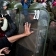 High school students confront police blocking their march for education reform in downtown Santiago, Chile, Wednesday, June 15, 2016. Protesters are demanding free access to school for all ages, including university level. (AP Photo/Esteban Felix)