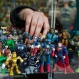 A woman places a toy figure of Captain America amid a collection of super hero and comic action figures on a shelf at a used toys' shop in Santiago, Chile, Friday, June 24, 2016. (AP Photo/Esteban Felix)