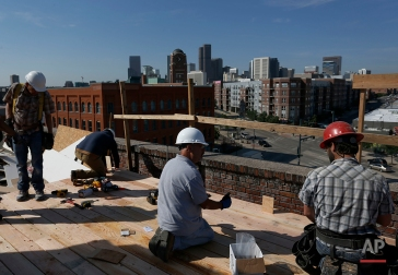 In this June 29, 2016 photo, a construction team works on the rooftop of a high-end office structure in downtown Denver. One of the fastest growing economies in the nation, Denver's current success has brought with it a high demand for new housing and office space. (AP Photo/Brennan Linsley)