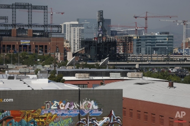 """In this June 29, 2016 photo, cranes dot the landscape in downtown Denver. Richard Florida, a prominent urban theorist, argues that living in a booming city, with its high cost of living, can be tougher than living in a slowly depopulating rural area. """"People in urban and rural areas are living very different lives and experiencing the world very differently,"""" Florida said. (AP Photo/Brennan Linsley)"""