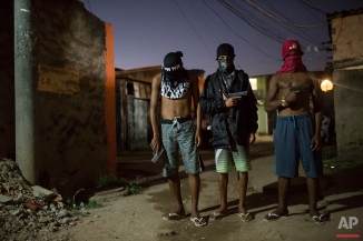 In this July 11, 2016 photo, young drug traffickers pose for photos holding their guns at a slum in Rio de Janeiro. Teenage boys openly tote guns as they run in flip-flops through a maze of alleys. When Associated Press journalists visit areas with authorization from the gangs, the ones who agree to be photographed cover their faces so they can't be identified. (AP Photo/Felipe Dana)