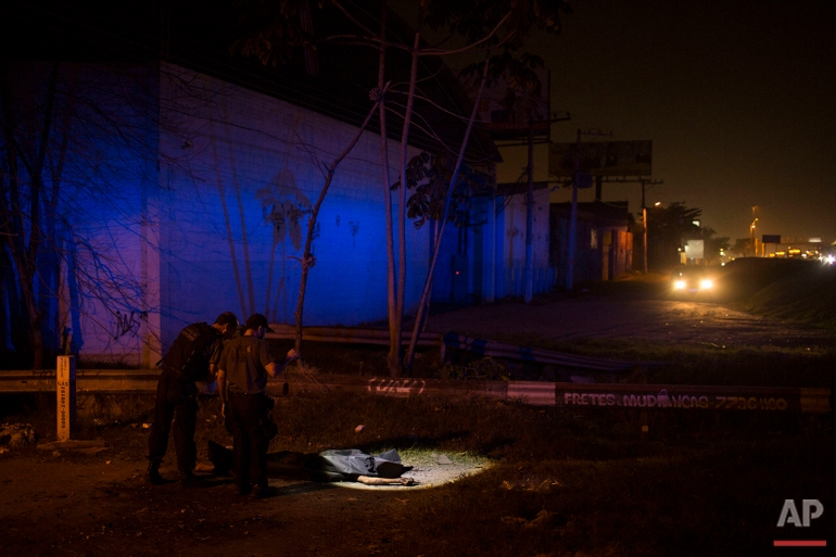In this July 15, 2016 photo, police officers use a flashlight to inspect the crime scene where the body of an alleged thief was found on a roadside in Nova Iguacu, greater Rio de Janeiro. Gruesome scenes of death and impunity play out daily in Rio's hundreds of shantytowns, known as favelas. (AP Photo/Felipe Dana)