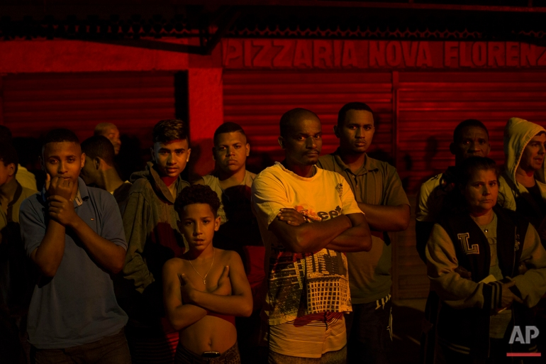 In this July 15, 2016 photo, residents watch as police work the crime scene where a man was murdered in Mage, greater Rio de Janeiro. Scenes of impunity and violence play out daily in many of Rio's hundreds of slums, known here as favelas, and other outlying areas. The vast majority of killings are the result of heavily armed gangs who frequently shoot it out in turf wars. (AP Photo/Felipe Dana)