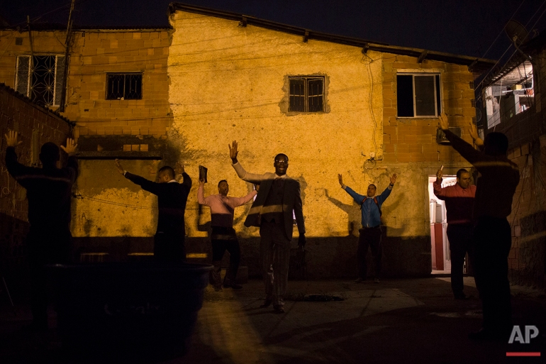 In this July 16, 2016 photo, Pastor Nilton, back right in blue, rejoices with members of his church after learning that residents will allow him to hold a prayer service in their courtyard, in a gang-ruled slum in Rio de Janeiro. Pastor Nilton, a former drug trafficker, spends his energy looking to convert the teenage boys who serve as security guards, lookouts and distributors for the drug lords operating in the slums. (AP Photo/Felipe Dana)
