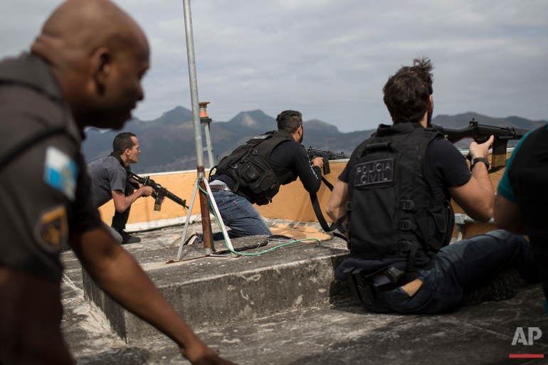 """In this July 7, 2016 photo, police exchange gunfire with drug traffickers at the """"pacified"""" Alemao slum complex in Rio de Janeiro. Half a dozen officers had entrenched themselves behind a cable car station while they shot it out with suspected drug traffickers in the sprawling cluster of slums in north Rio. Shootouts erupt daily, even in slums where community policing programs had successfully rewritten the narrative in recent years. (AP Photo/Felipe Dana)"""