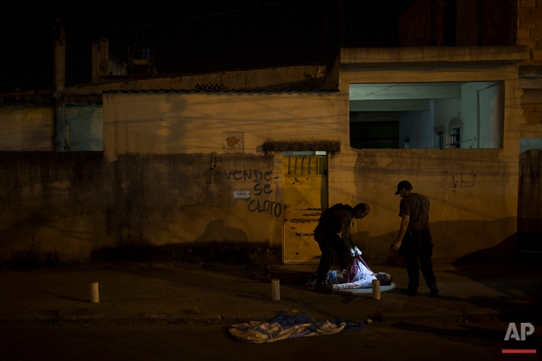 In this July 16, 2016 photo, police responding to a call find the body of a young black man in the middle of a residential street in Caxias, greater Rio de Janeiro. Rio's ambitious security push to bring crime down and seize control of certain slums ahead of the 2016 Summer Games is crumbling. Overall slayings are on the rise in 2016, the victims overwhelmingly young, black men. (AP Photo/Felipe Dana)