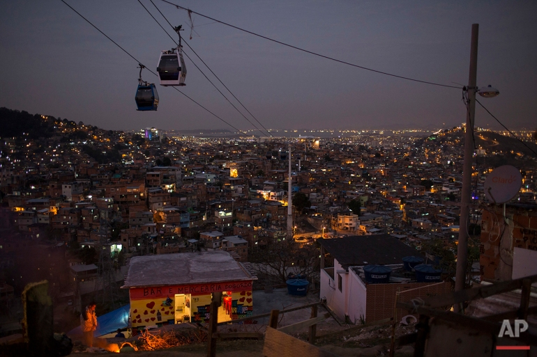 In this July 19, 2016 photo, cable cars transport commuters over the Complexo do Alemao, a sprawling cluster of slums in north Rio de Janeiro. Just a short drive from upscale Rio districts like Ipanema and Copacabana, steep and narrow entryways lead to slums where poverty and gun violence dominate daily life for hundreds of thousands of residents. (AP Photo/Felipe Dana)