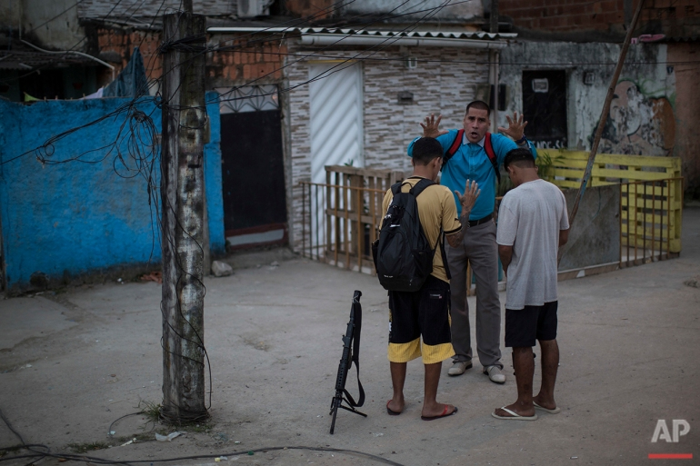 In this July 16, 2016 photo, pastor Nilton blesses two young drug traffickers at a slum in Rio de Janeiro. Many of the young drug traffickers have an immense respect for the pastor, a former drug trafficker. It's not uncommon to see young men set their weapons down, but only long enough to receive his blessing. (AP Photo/Felipe Dana)