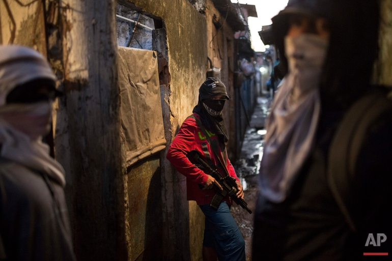 In this July 11, 2016 photo, masked teenage boys pose for photos holding their guns at a slum in Rio de Janeiro. The teens are security guards, lookouts and distributors for drug lords operating just a few miles (kilometers) from where hundreds of thousands and tourists and athletes will be for the Aug. 5-21 Olympic Games. (AP Photo/Felipe Dana)