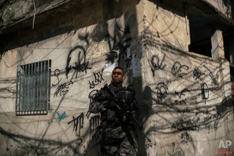"""In this June 29, 2016 photo, a police officer takes position during an operation against drug traffickers at the """"pacified"""" Jacarezinho slum in Rio de Janeiro. The number of people killed by police has spiked in the past two years after dropping significantly the previous six. Overall murders are also on the rise in the first half of 2016, just as officials wanted to use the Aug. 5-21 Olympic Games to showcase the city as a tourist destination. (AP Photo/Felipe Dana)"""