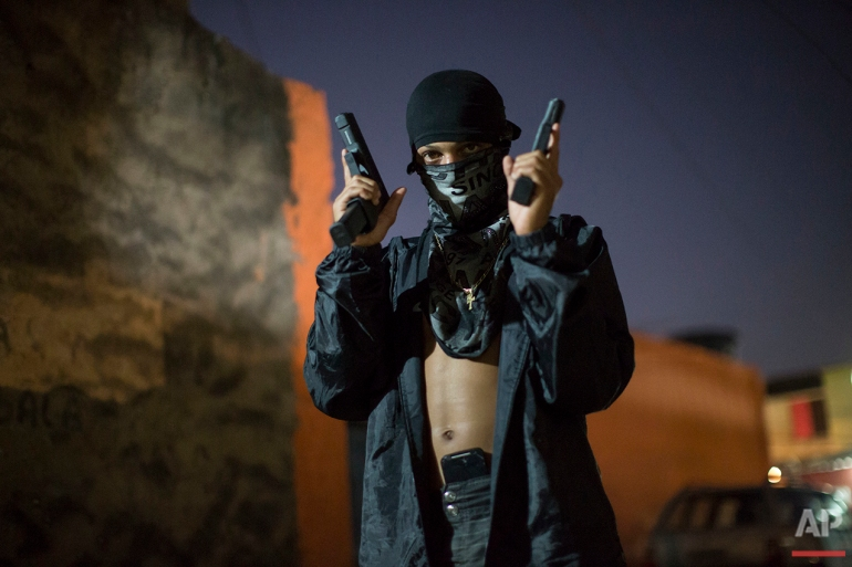 In this July 11, 2016 photo, a young, masked drug trafficker poses for photos holding his guns at a slum in Rio de Janeiro. Teenagers openly tote guns while they work as guards, lookouts and distributors for drug lords operating just a few miles (kilometers) from where hundreds of thousands and tourists and athletes will be for the Aug. 5-21 Olympic Games. (AP Photo/Felipe Dana)