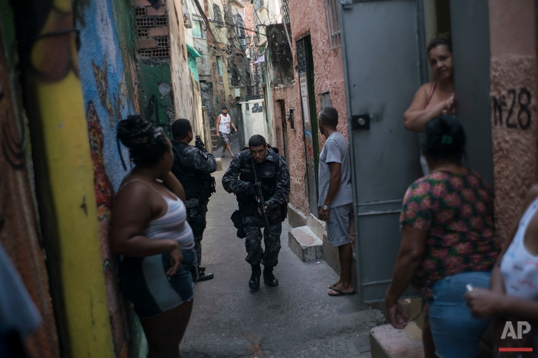 """In this June 29, 2016 photo, a police officer patrols among residents during an operation against drug traffickers at the """"pacified"""" Jacarezinho slum in Rio de Janeiro. The Pacification Police Units, known by the Portuguese acronym UPP, were created in 2008, setting up community stations in at-risk areas, mostly near sports venues, posh tourist districts and downtown. A drug gang leader called the program a """"facade."""" He said that drug dealers were initially worried and kept a low profile, but soon it was back to business as usual. (AP Photo/Felipe Dana)"""