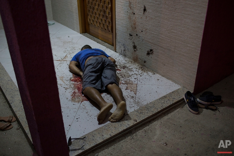 This July 13, 2016 photo shows the body of a man who was taken from the inside of his home and shot dead at the entrance of his home in Nova Iguacu, greater Rio de Janeiro. Scenes of impunity and violence play out daily in many of Rio's hundreds of slums, known here as favelas, and other outlying areas. Police believe this homicide was gang-related. (AP Photo/Felipe Dana)