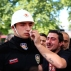 A relative, right, of one of the victims of Tuesday's explosion, wipes the face of a Turkish police officer, serving as a honor guard, during the funeral procession for two of the victims at Fatih mosque in Istanbul, Wednesday, June 8, 2016. The bomb attack, targeting a bus carrying riot police during rush hour traffic in Istanbul, has killed a number of people and wounded dozens of others. (AP Photo/Lefteris Pitarakis)