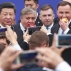 Chinese President Xi Jinping, left, and Polish President Andrzej Duda, right, eat an apple as they view the first China Railway Express train, that rolled into the Polish capital from China ending a 13-day trip from Chengdu, capital of the central Sichuan province to Warsaw, Poland, on Monday, 20 June 2016. The visit is intended to boost China's infrastructure investments in Europe, and opening China's market to Poland's foods. (AP Photo/Czarek Sokolowski)