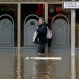 A woman tries to find a way out in a flooded street downtown Longjumeau, south of Paris, Thursday, June 2, 2016. Floods inundating parts of France and Germany have left five people reported dead and thousands trapped in homes or cars, as rivers have broken their banks from Paris to Bavaria. (AP Photo/Francois Mori)