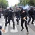 Riot police officers clash with protestors during a protest against a labor law bill, in Paris, Tuesday, June 28, 2016. The Socialist government wants the reforms to make it easier to lay off employees, allow temporary extension of the work week and give company deals priority over industry-wide deals. (AP Photo/Thibault Camus)