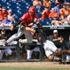 Arizona's Cesar Salazar, left, is tagged out at home plate by Oklahoma State catcher Collin Theroux, right, as he attempts to score from third base on a single hit to center field by Zach Gibbons in the sixth inning of an NCAA men's College World Series baseball game, Friday, June 24, 2016, in Omaha, Neb. (AP Photo/Ted Kirk)
