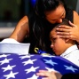 Kristy Villasenor, partner of Dallas police officer Patrick Zamarripa, shares a moment with her son, Dylan Hoover, after a funeral service for Zamarripa on Saturday, July 16, 2016, at Wilkerson-Greines Athletic Center in Fort Worth, Texas. Zamarripa was one of the five officers killed July 7 by a lone gunman during a march to protest recent fatal shootings of black men in Minnesota and Louisiana by police. (Ashley Landis /The Dallas Morning News via AP, Pool)