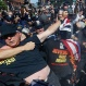 A law enforcement officer clashes with protester who is holding a burning American flag, Wednesday, July 20, 2016, in Cleveland, during the third day of the Republican convention. (AP Photo/John Minchillo)