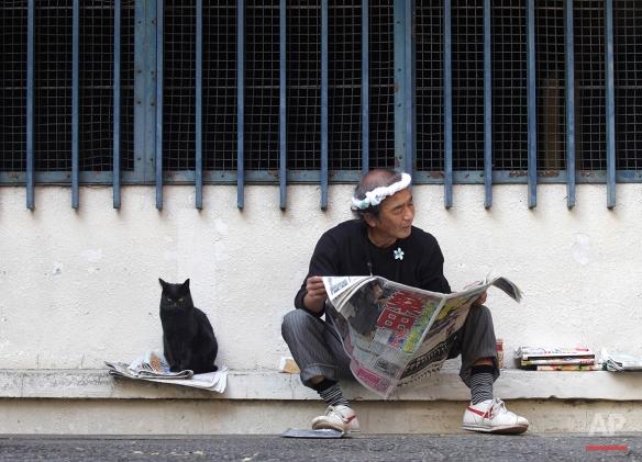 A cat sits by a man reading a newspaper at a park in Tokyo, Monday, Nov. 7, 2011. (AP Photo/Shizuo Kambayashi)
