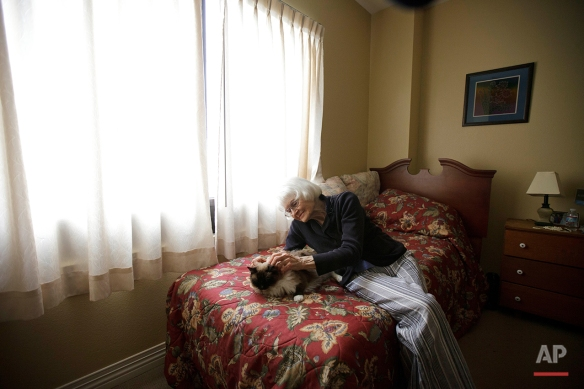 Joyce Kavanagh pets her cat as she sits in her room at the Silverado Senior Living Center Tuesday, May 1, 2012, in Encinitas, Calif. At the senior center, residents are encouraged to bring their pets. Everything from miniature horses to chinchillascan be found on the grounds, and residents benefit from frequent contact with the pets. (AP Photo/Gregory Bull)