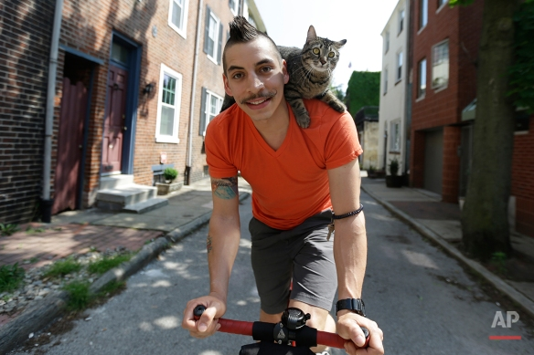 In this Tuesday, May 21, 2013 photo, bicyclist Rudi Saldia and his cat Mary Jane pose for a portrait during an interview with the Associated Press in Philadelphia. Saldia often buzzes around Philadelphia with his year-old feline Mary Jane perched on his shoulder. Their urban adventures have turned heads on the street and garnered big hits on YouTube. (AP Photo/Matt Rourke)