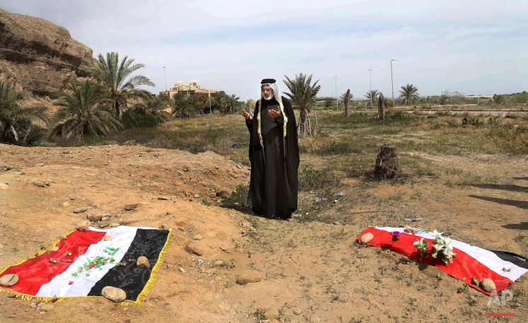 In this April 3, 2015 photo, an Iraqi man prays for his slain relative at the site of a mass grave believed to contain the bodies of Iraqi soldiers killed by Islamic State group militants when they overran Camp Speicher military base in Tikrit, Iraq, in June 2014. An analysis by The Associated Press has found 72 mass graves left behind by Islamic State extremists in Iraq and Syria, and many more are expected to be discovered as the group loses territory. (AP Photo/Khalid Mohammed)