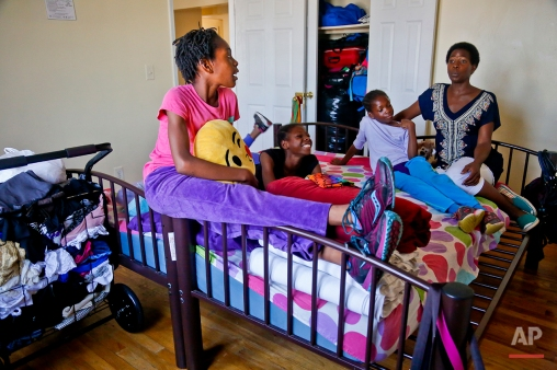"""In this Wednesday, July 20, 2016 photo, Tonia Handy, far right, and her daughters, Rainn, 10, far left, Tai, 11, second from left, and Brooke, 8, second from right, together in the bedroom of their apartment in a Brooklyn shelter, in New York. """"Some families meet at the dinner table, we have these mattresses that were put together by two twin beds and that's our meeting place,"""" said Handy. """"We do everything in that bed. It's somewhere to connect."""" (AP Photo/Bebeto Matthews)"""