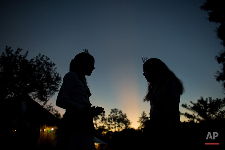 In this June 23, 2016 photo, girls talk at sunrise after an all night religious service of the church of the doctrine of the Holy Daime in Ceu do Mapia, Amazonas state, Brazil. For the service women wear shiny white crowns on their heads, green sashes over their shoulders and green belts around their waist. (AP Photo/Eraldo Peres)