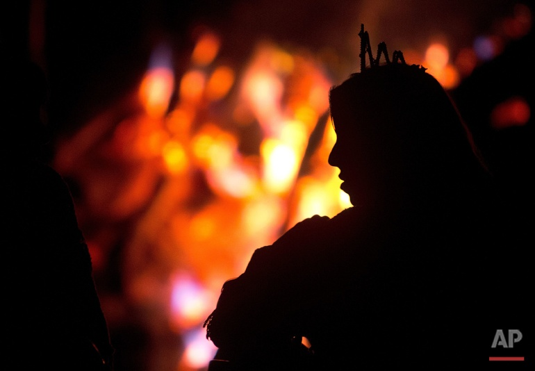 In this June 22, 2016 photo, a woman wearing a white crown warms up next to a bonfire during a break in the service of the church of the doctrine of the Holy Daime, in Ceu do Mapia, Amazonas state, Brazil. During the all night service men and women line up in two separate rows to drink the psychedelic tea after making the sign of the cross. They then sing together prayers and psalms in a large circle. (AP Photo/Eraldo Peres)