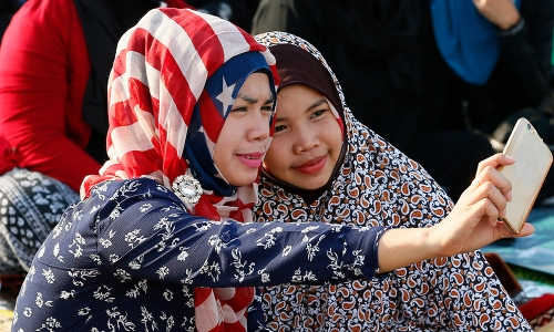 """Filipino Muslims take a selfie photo as they gather at Rizal Park for Eid'l Fitr, to mark the end of the holy month of Ramadan in Manila, Philippines, on Wednesday, July 6, 2016. The rest of the world may think Americans eat a lot of burgers, have huge shopping malls and are ruled by an arrogant government. And yet the """"Ugly American,"""" it would seem, isn't all bad. Americans are also seen from afar as generous tippers, friendly, uncomplicated, rich and the standard bearers of freedom, equality, creativity and technological power. (AP Photo/Bullit Marquez)"""
