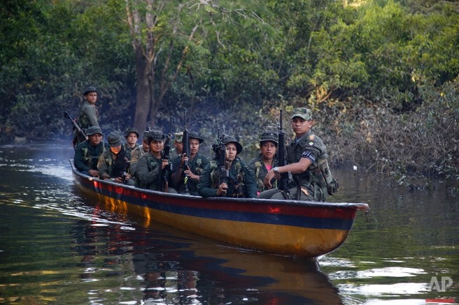 In this Aug. 11, 2016 photo, rebels of the 32nd Front of the Revolutionary Armed Forces of Colombia, or FARC, sit in a boat as they patrol the Mecaya river in the southern jungles of Putumayo, Colombia. As the country's half-century conflict winds down, with the signing of a peace deal perhaps just days away, thousands of FARC rebels are emerging from their hideouts and preparing for a life without arms. (AP Photo/Fernando Vergara)